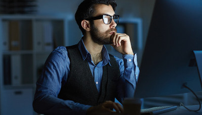 man thinking in front of computer screen