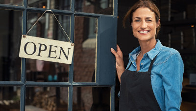 woman standing in front of store holding open sign